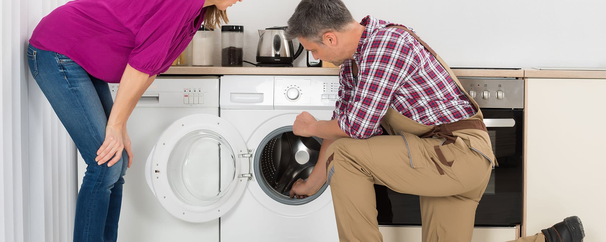 Woman Looking At Repairman Checking Washing Machine In Kitchen