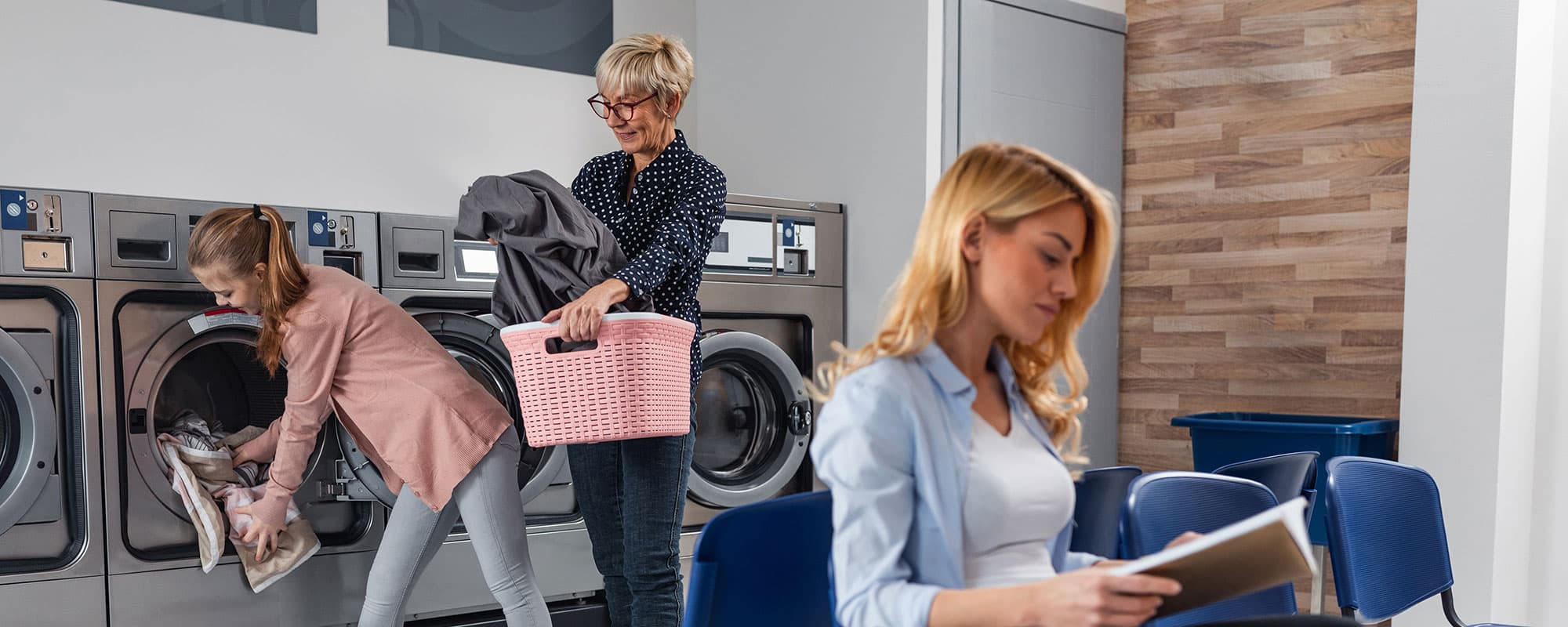 Shot of a grandmother and granddaughter using a washing machine while young woman reading a book beside