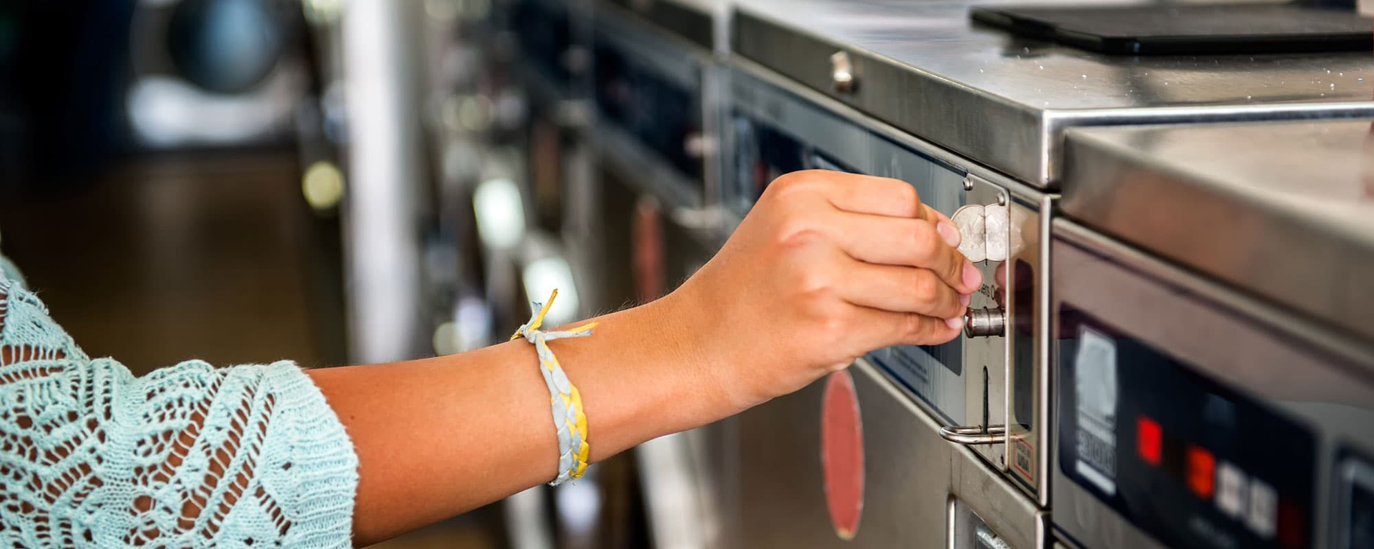 Photo of woman hand put quarter coin on the laundry machine in public laundry