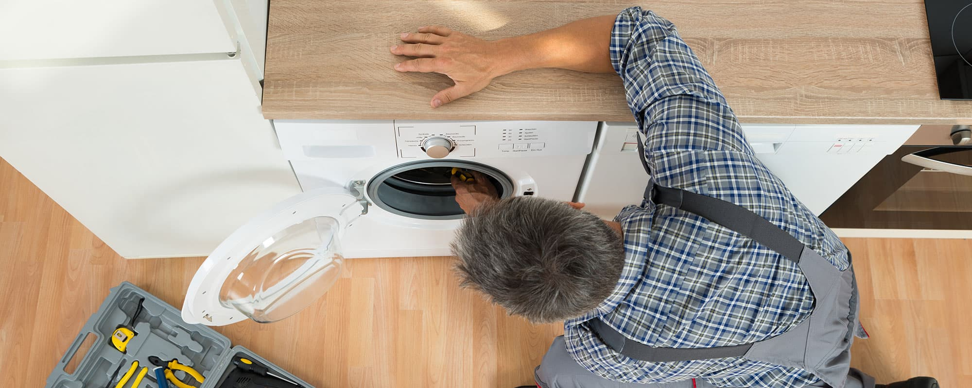 High angle view of handyman checking washing machine at home