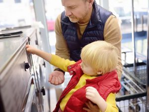 Little boy puts token in the washing machine in the public Laundry